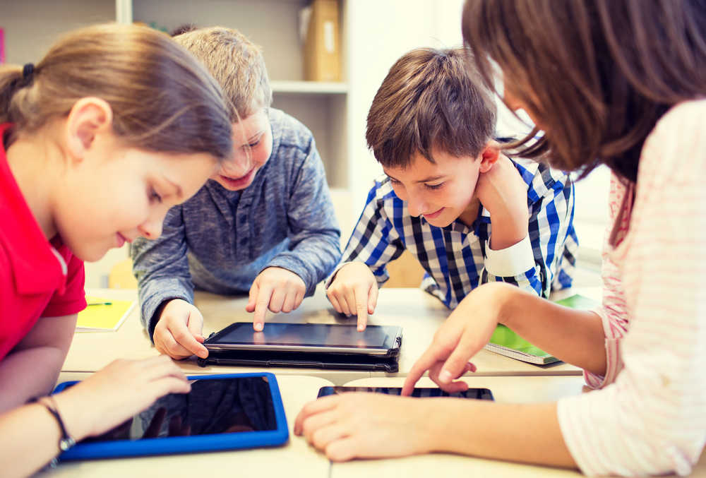 Children playing on computer tablets not knowing how to protect their privacy online