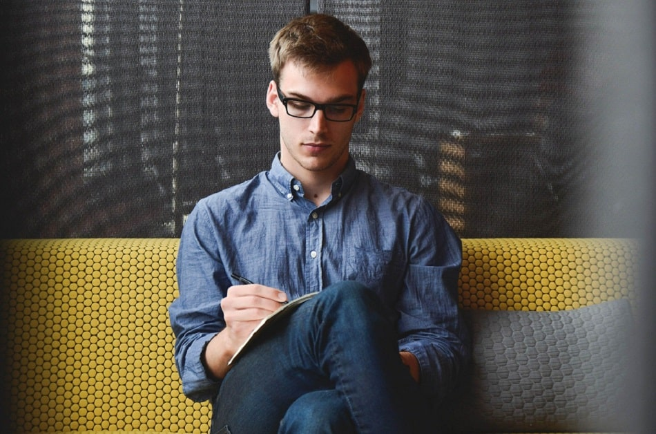 young professional man writing in notebook on a couch
