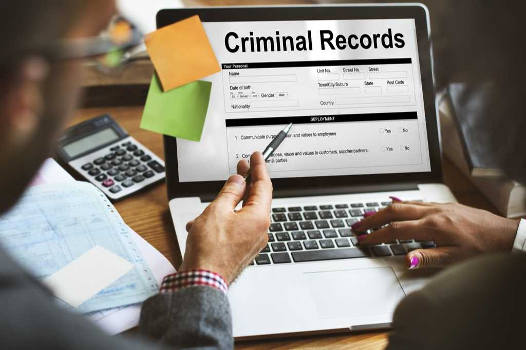 laptop with posted notes showing criminal records