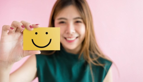 woman holding up smiley face card yellow